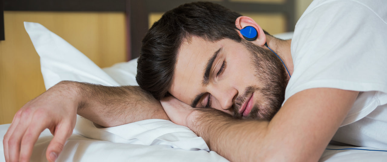 Man sleeping wearing blue Bedphones Sleep Headphones Gen. 3.5