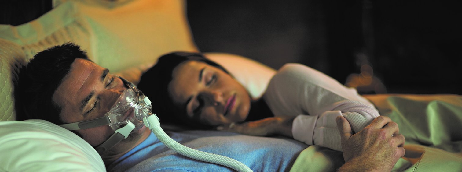 Couple Sleeping with CPAP Mask for Apnea Management