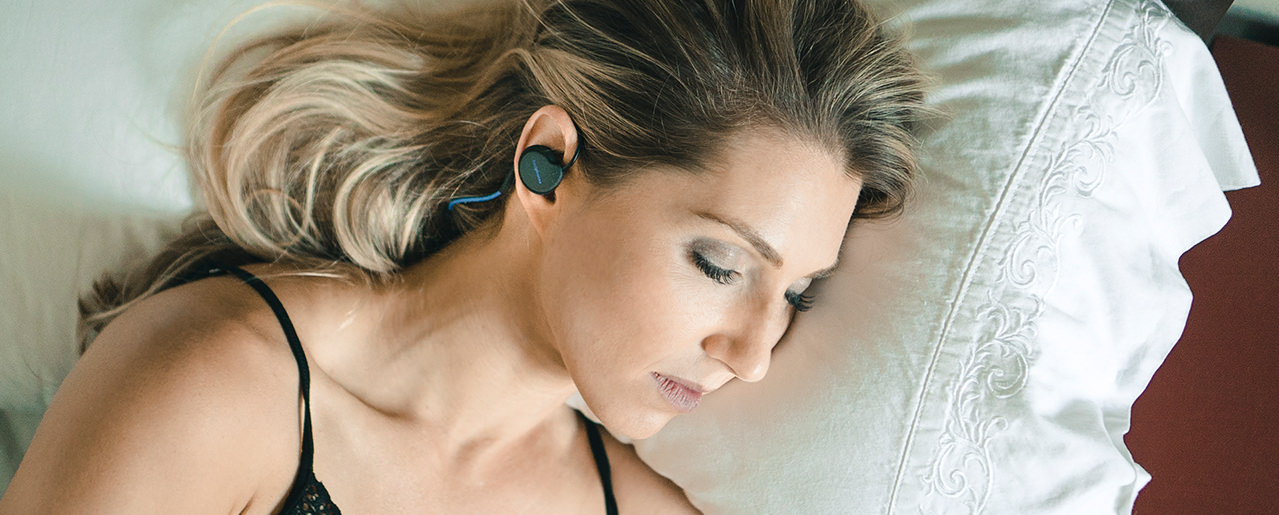 Woman sleeping on pillow wearing Bedphones Wireless Sleep Headphones