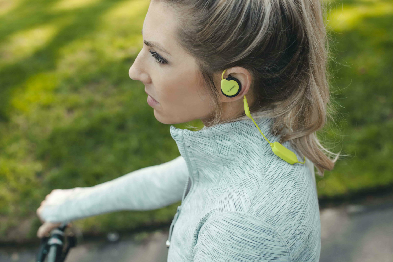 Woman riding bicycle while listening to Versafit Wireless Sport Headphones